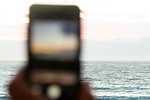 Sun setting  over ocean through a phone. Strait of Juan de Fuca, WA