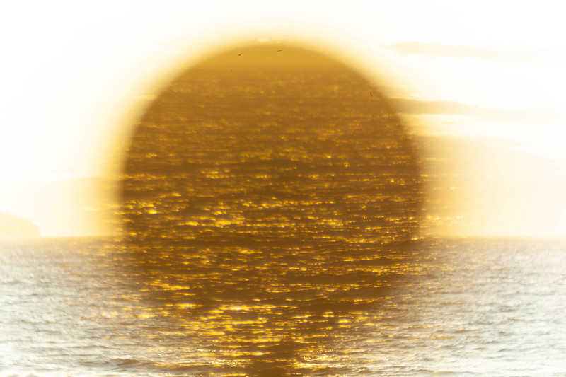 Sun setting  over ocean through telescope. Strait of Juan de Fuca, WA