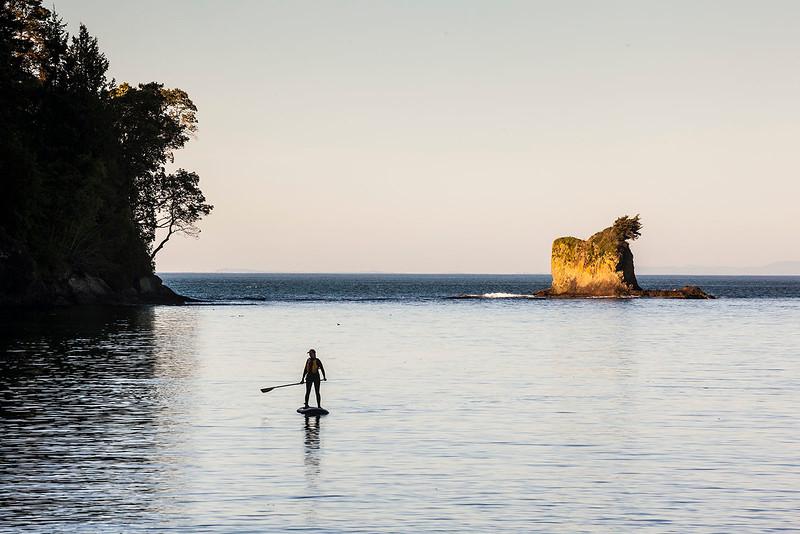 Paddle boarder on Freshwater Bay, WA USA