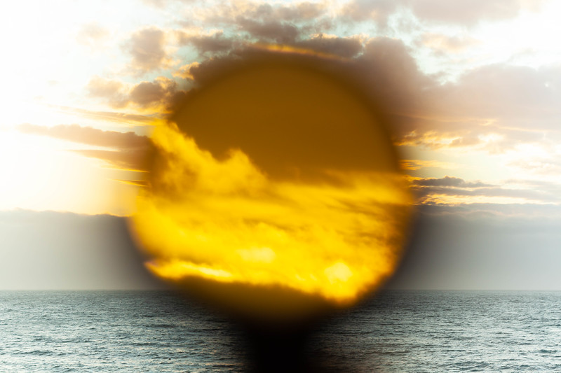 Sun setting  over ocean through telescope