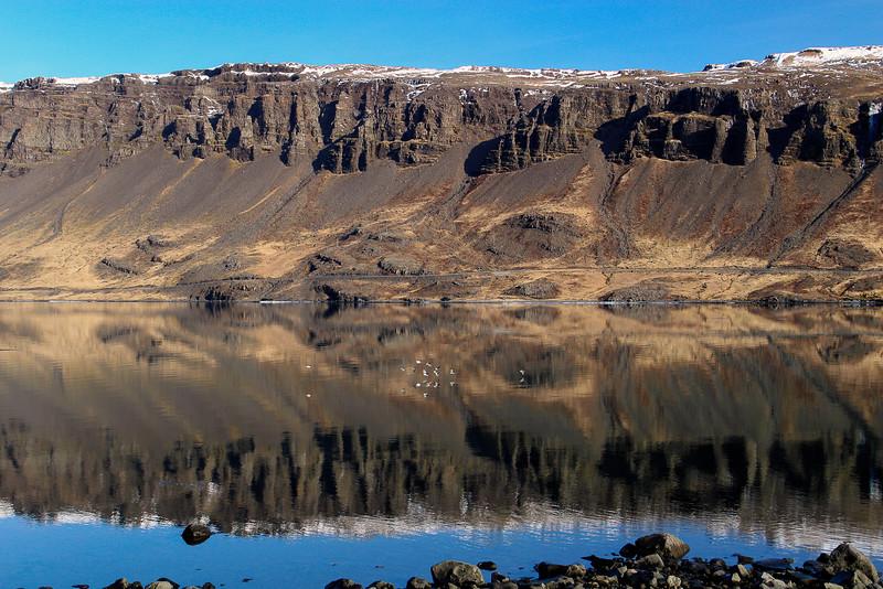 Mountain in still fjord