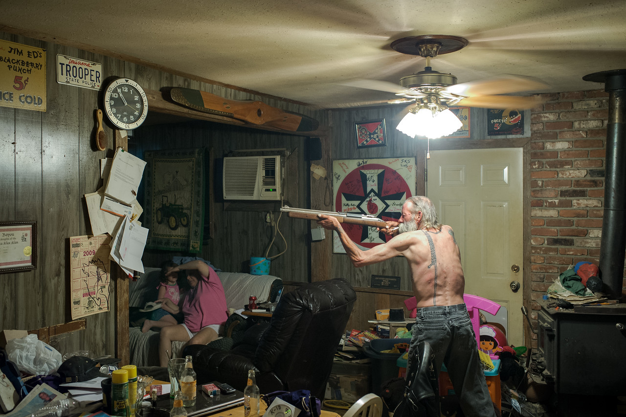 Carl, an Imperial Wizard of a southern-based Ku Klux Klan realm, takes aim with a pellet gun at a large cockroach on a piece of paper.
