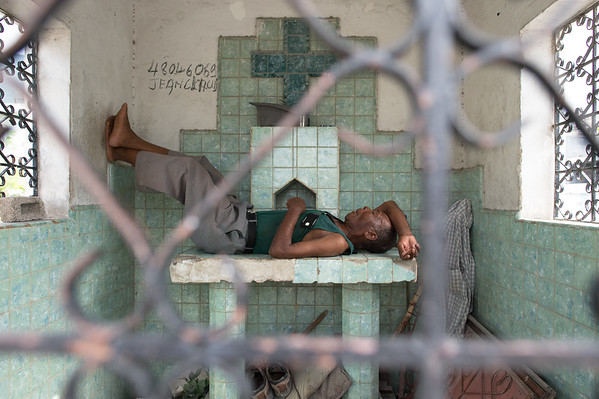 A husband naps in the tomb of his deceased wife. Grand Cimetiere (Grand Cemetery). Port-au-Prince, Haiti.