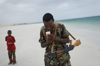 A TFG solider lights a cigarette while patrolling the beach in the Shangani District of Mogadishu. This old city was once a major attraction in Somalia, bringing in tourists from all over the world. Today it is completely destroyed and virtually lifeless from years of civil war.
