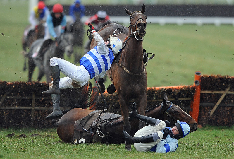 Horse Racing<br /> Cheltenham Festival 2010 Day 4, Cheltenham Racecourse<br /> 19/03/2010. Credit: Dan Rowley/Colorsport<br /> The Albert Bartlett Novices' Hurdle Race<br /> Jockey Henry Oliver lies on the ground with his horse Restless Harry who fell at the last hurdle as Fionnegas unseats jockey D J Casey over the top of them