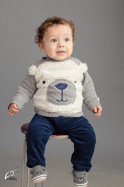 Caucasian baby sitting on stool isolated inside studio