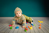 Small boy with his toys scattered around him on wooden floor