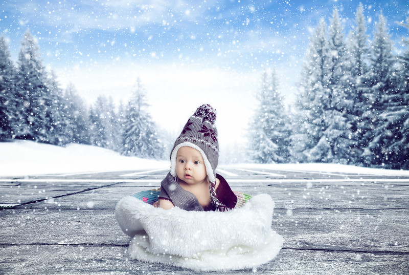 Caucasain baby sitting inside basket during snow fall