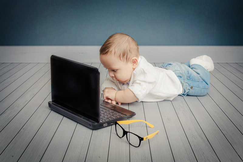Small boy looking to computer while crawling
