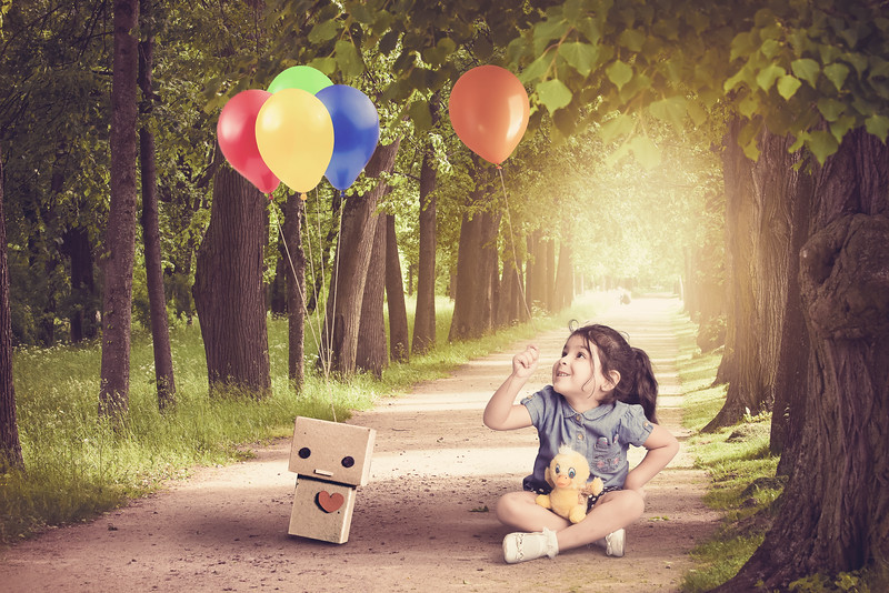 Small girl sitting on park ground playing with balloons