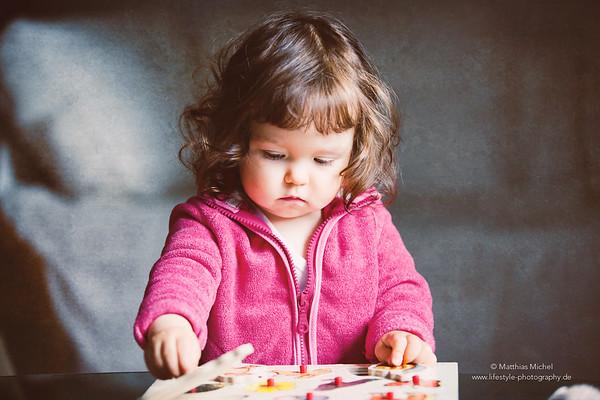 Kleines Mädchen spielt mit Holzpuzzle