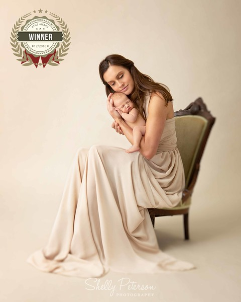beautiful woman with brown hair holding her sweet newborn boy in her arms as she sits in an antique chair. an award winning image from AFNS awards