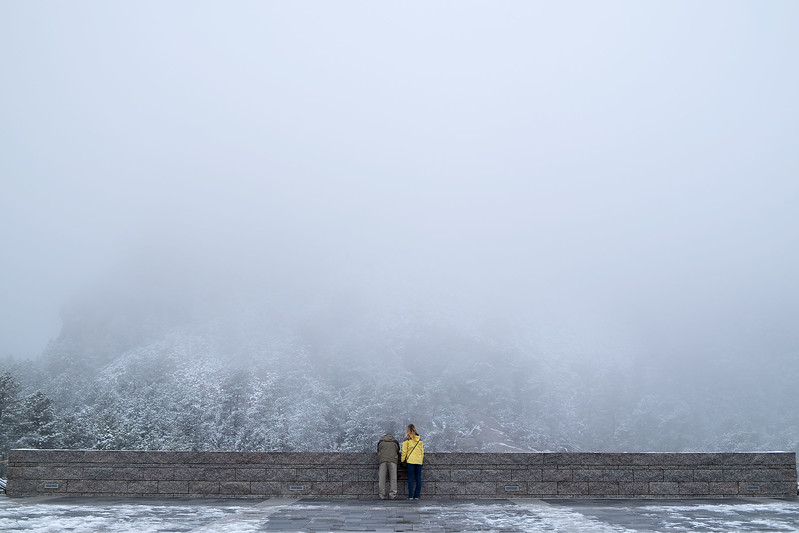 Couple Waiting for the Fog to Clear at Mt Rushmore in Winter