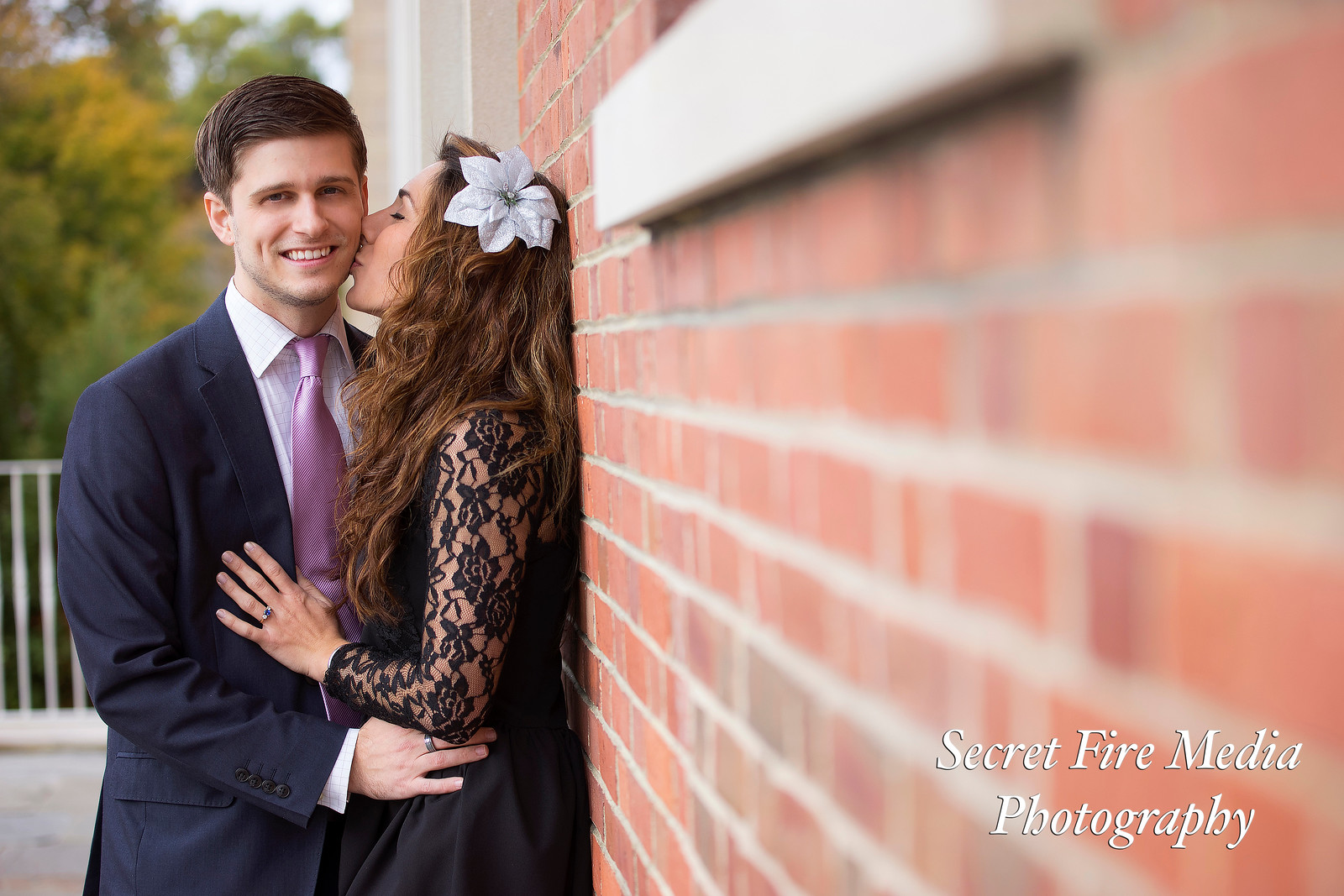 Bride Kisses Groom by a brick wall at their Albany Enagement Shoot at Siena College