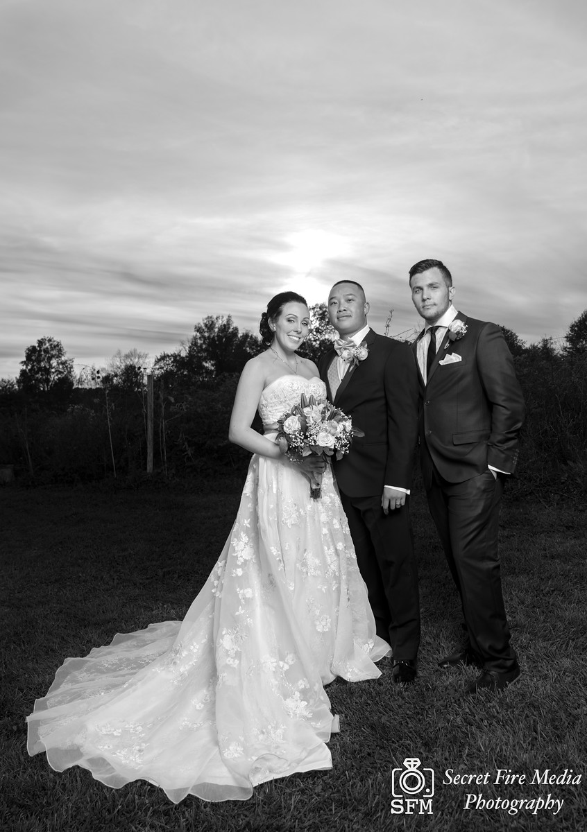 Bride and groom pose with her brother at sunset for a Hudson Valley Wedding Photo At Lippincott Manor in Walkill New York