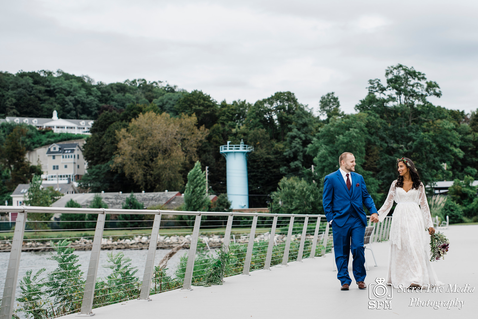 Bride and groom hold hands and walk on a pier at the Peekskill waterfront before a Hudson Valley Wedding at The Dramatic Hall in Peekskill New York