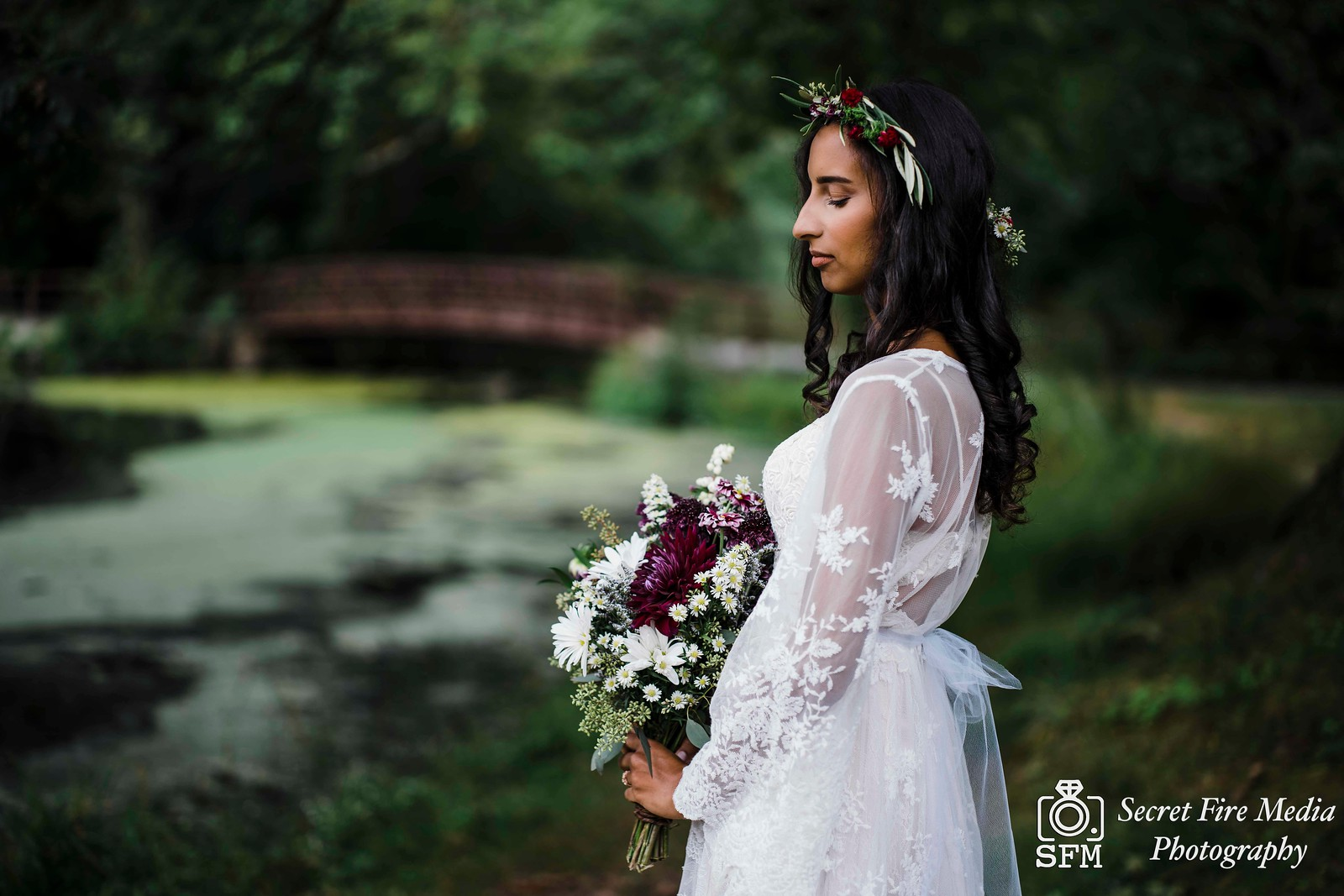 Bride poses with bouquet by a lake at Blue Mountain Reservation before a Hudson Valley Wedding at The Dramatic Hall in Peekskill New York