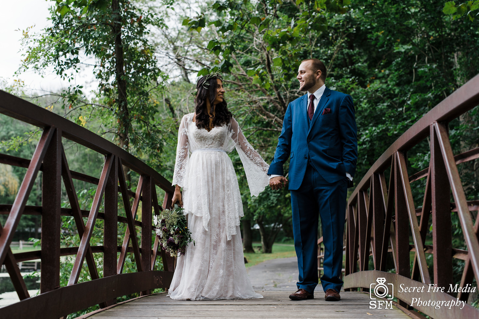 Bride and groom hold hands on a rustic metal bridge at Blue Mountain Reservation before a Hudson Valley Wedding at The Dramatic Hall in Peekskill New York