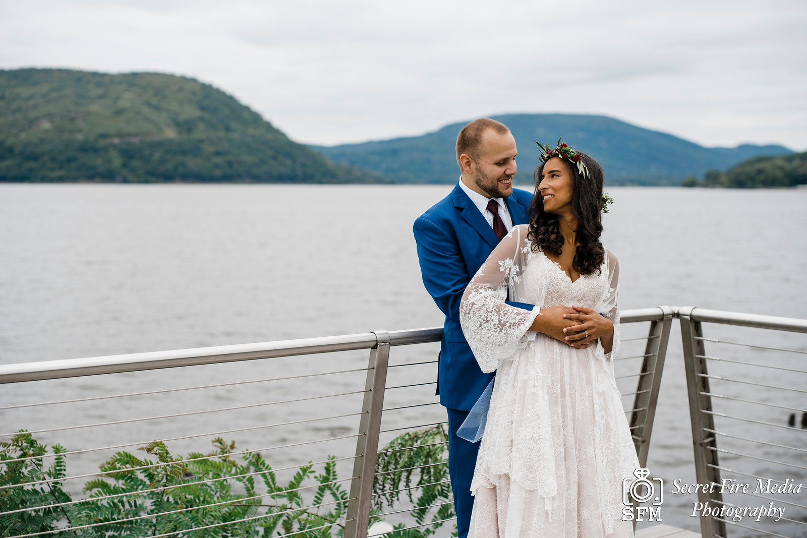 Bride and groom smile by the water at the Peekskill waterfront before a Hudson Valley Wedding at The Dramatic Hall in Peekskill New York