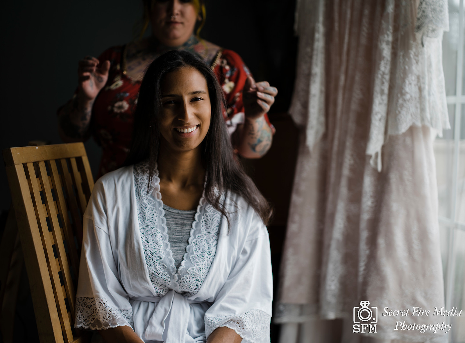 Bride smiling for a photo getting her hair done before a Hudson Valley Wedding at The Dramatic Hall in Peekskill New York