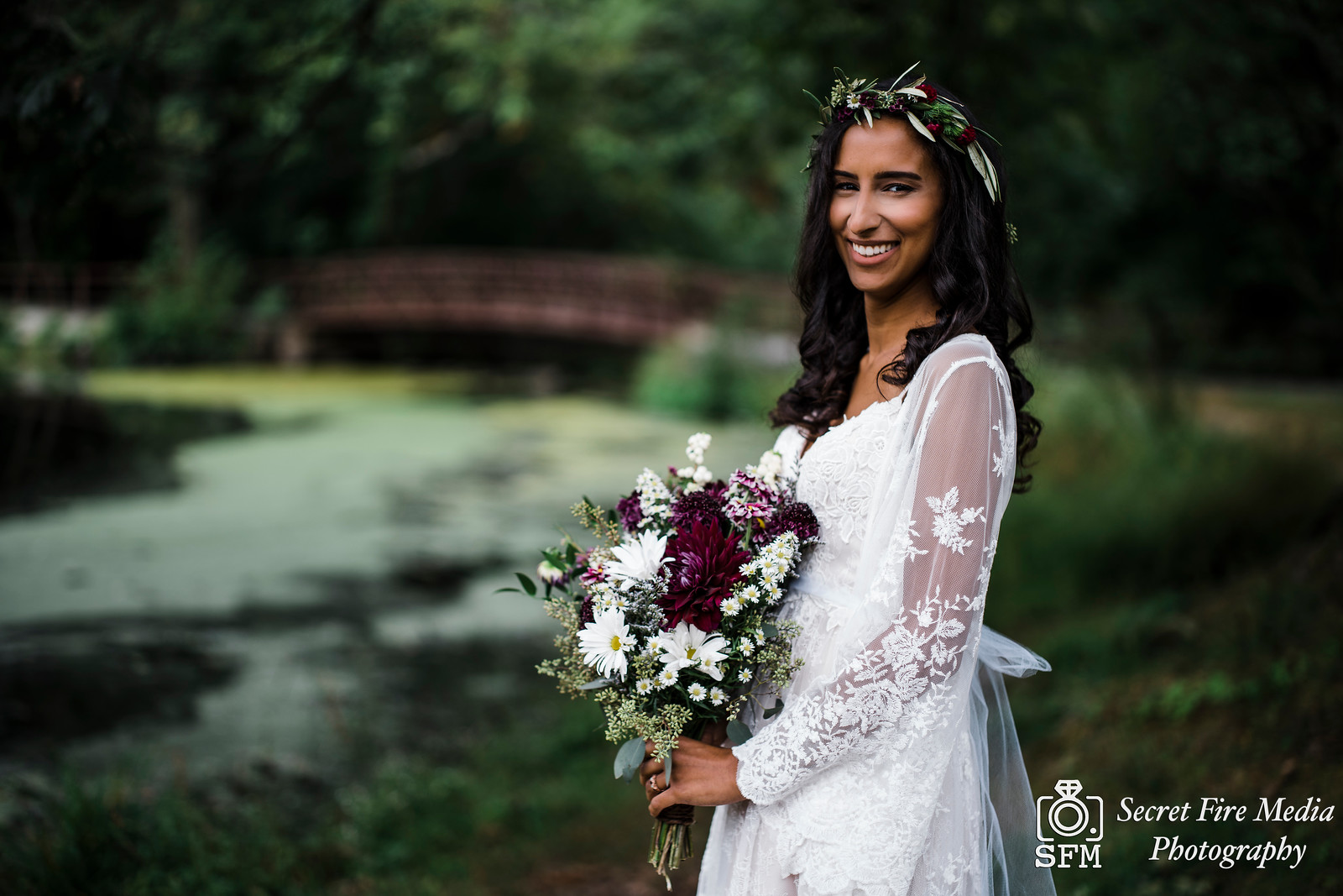Bride poses with bouquet by a lake and smiles at Blue Mountain Reservation before a Hudson Valley Wedding at The Dramatic Hall in Peekskill New York