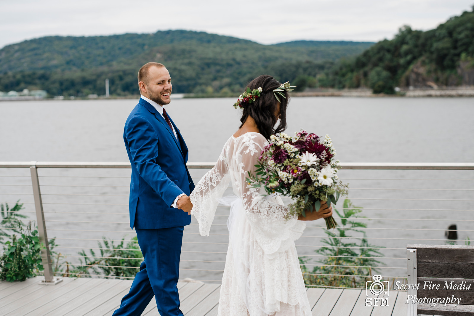 Bride and groom walk together on a pier at the Peekskill waterfront before a Hudson Valley Wedding at The Dramatic Hall in Peekskill New York