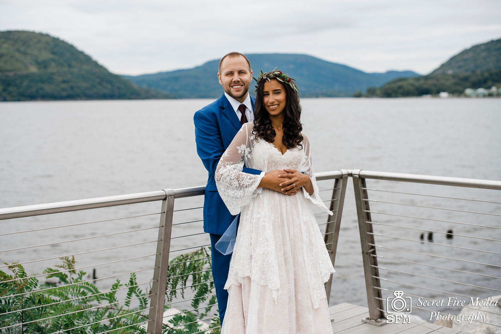 Bride and groom pose for a photo by the water at the Peekskill waterfront before a Hudson Valley Wedding at The Dramatic Hall in Peekskill New York