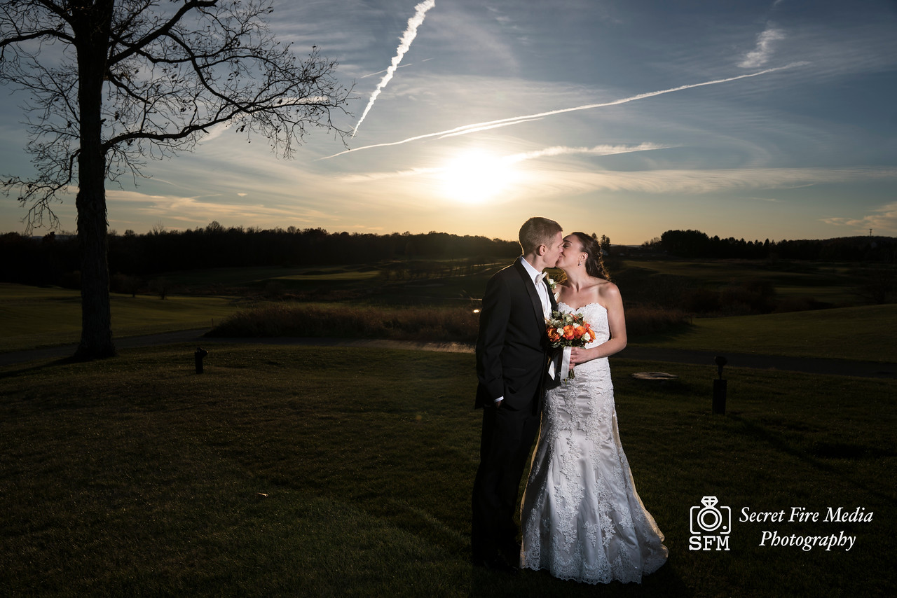 Bride and groom kiss by a sunset before her Hudson Valley Wedding At Links At Union Vale in New York
