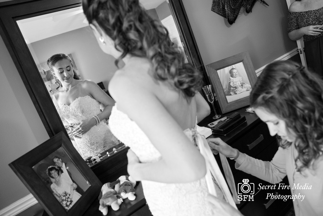 Bridesmaid helps bride into dress before her Hudson Valley Wedding At Links At Union Vale in New York