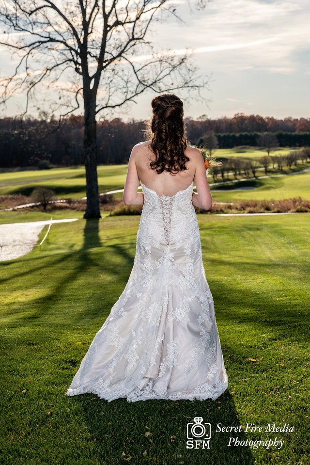 Bride poses by a field before her Hudson Valley Wedding At Links At Union Vale in New York