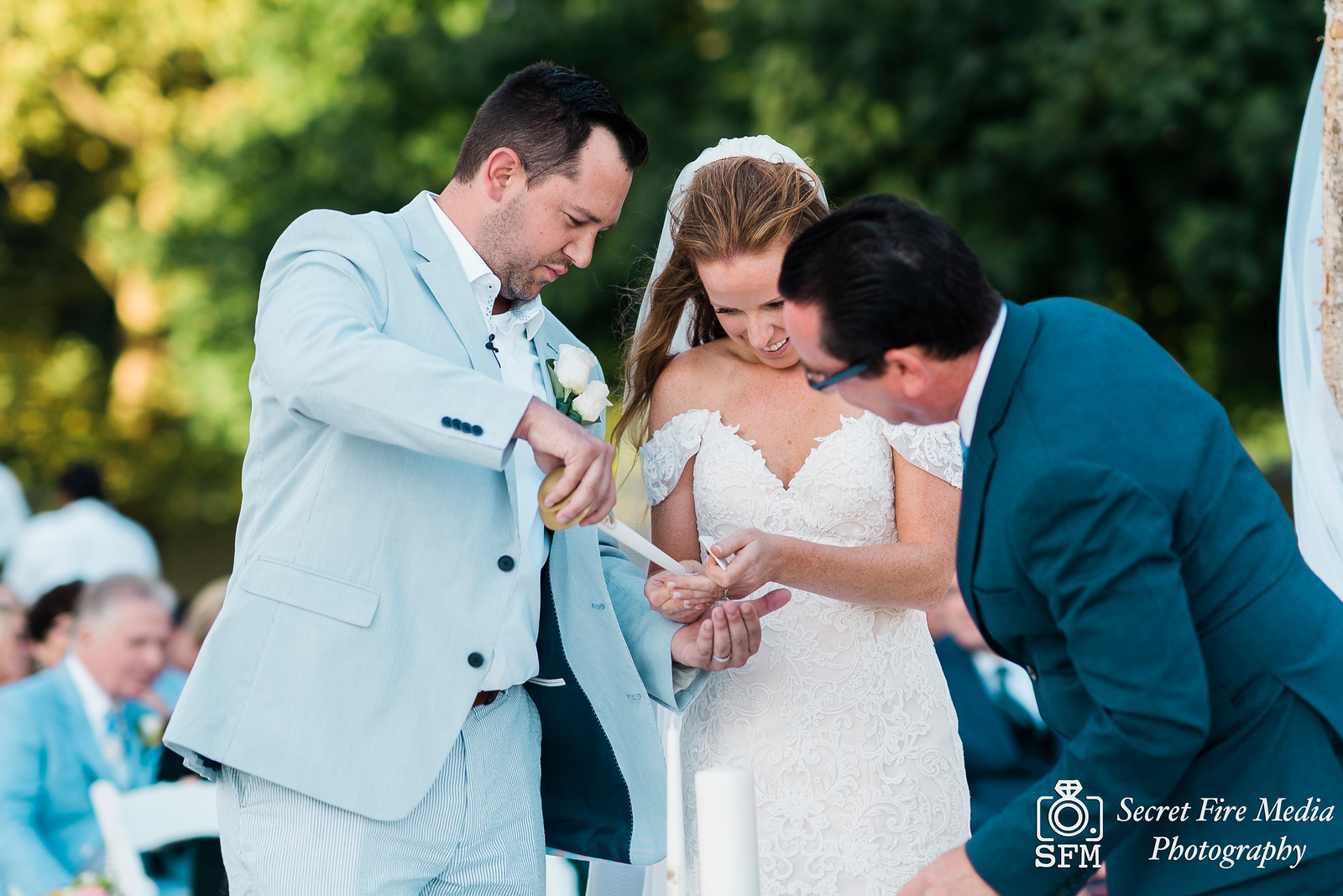 Bride and groom try to light candle at a ceremony on a beach at a Hudson Valley Wedding At Mamaroneck Beach and Yatch Club