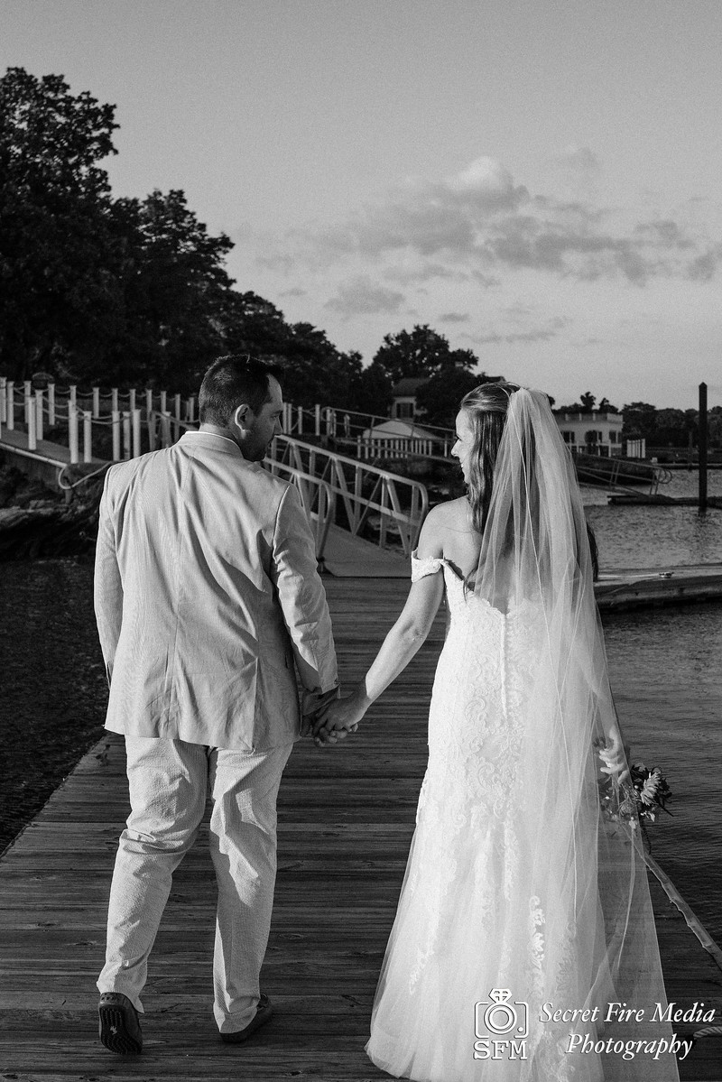 Black and White photo Bride and groom on a dock at a Hudson Valley Wedding At Mamaroneck Beach and Yatch Club