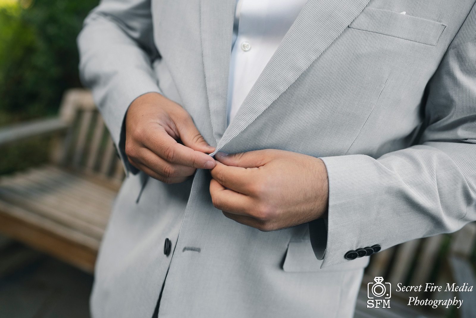 Groom buttons jacket at a Hudson Valley Wedding At Mamaroneck Beach and Yatch Club