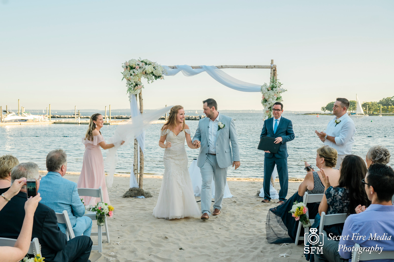 Bride and groom are married at a ceremony on a beach at a Hudson Valley Wedding At Mamaroneck Beach and Yatch Club