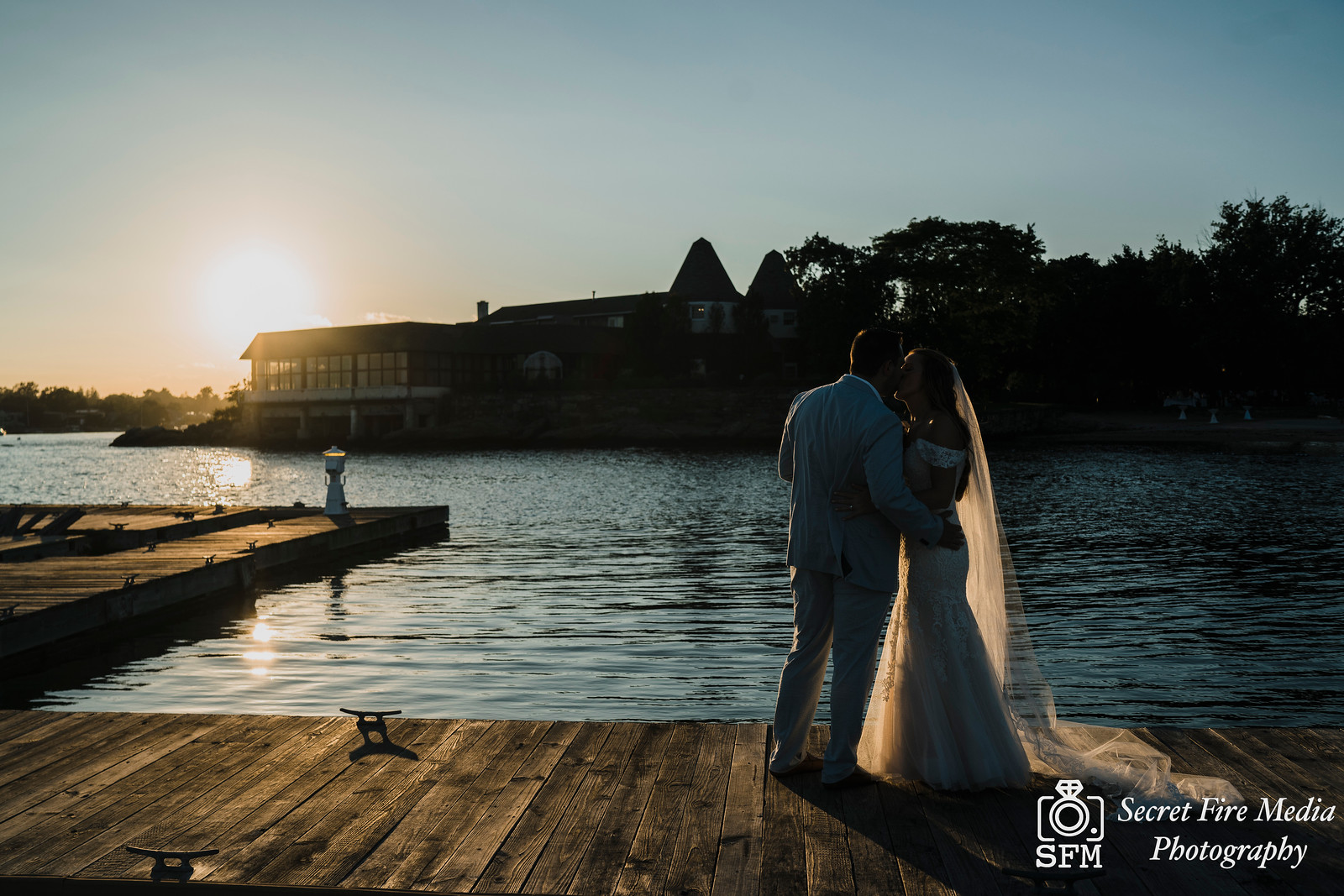 Bride and groom kiss on the dock at a Hudson Valley Wedding At Mamaroneck Beach and Yatch Club