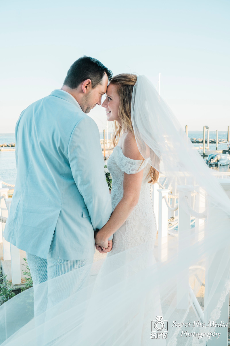 Bride and groom touch heads on the dock at a Hudson Valley Wedding At Mamaroneck Beach and Yatch Club