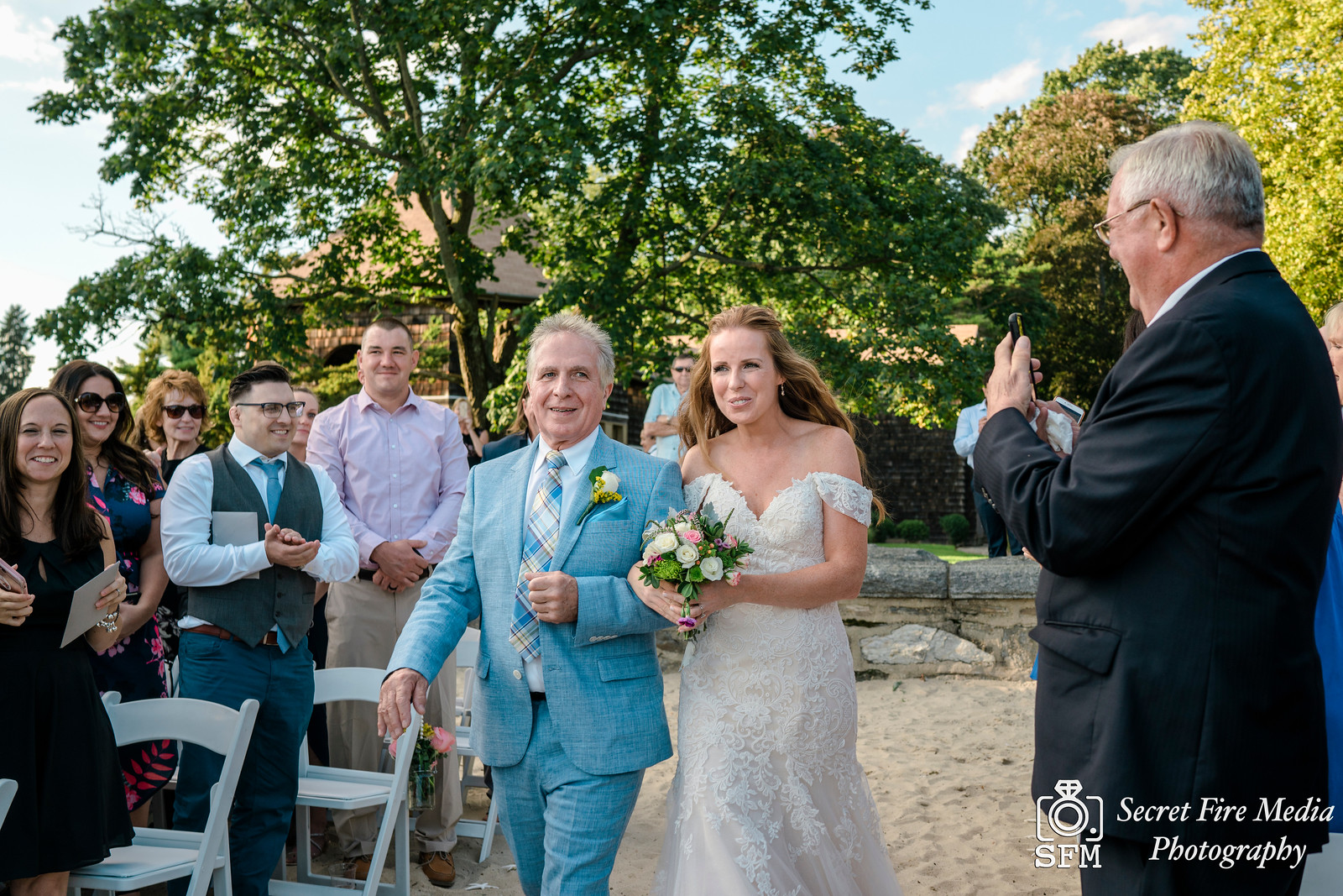 Father walks bride down the aisle at a ceremony on a beach at a Hudson Valley Wedding At Mamaroneck Beach and Yatch Club