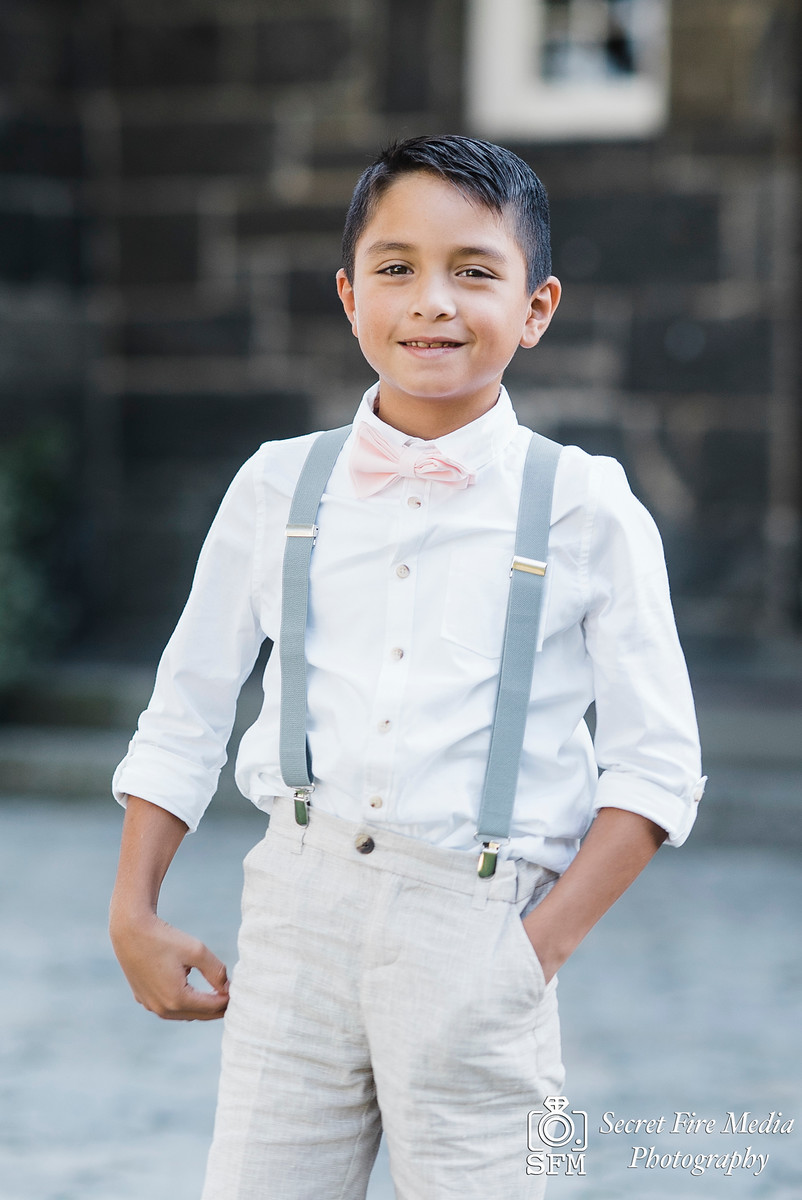Ring Bearer infront of a brick wall at a Hudson Valley Wedding At Mamaroneck Beach and Yatch Club