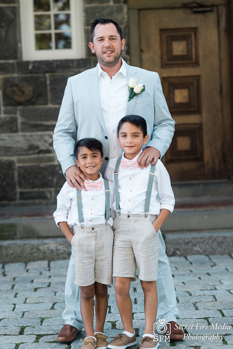 Groom and ring bearers infront of a brick wall at a Hudson Valley Wedding At Mamaroneck Beach and Yatch Club