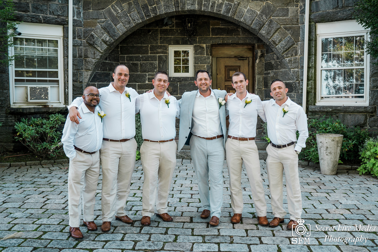 Groom and groomsmen infront of a brick wall at a Hudson Valley Wedding At Mamaroneck Beach and Yatch Club