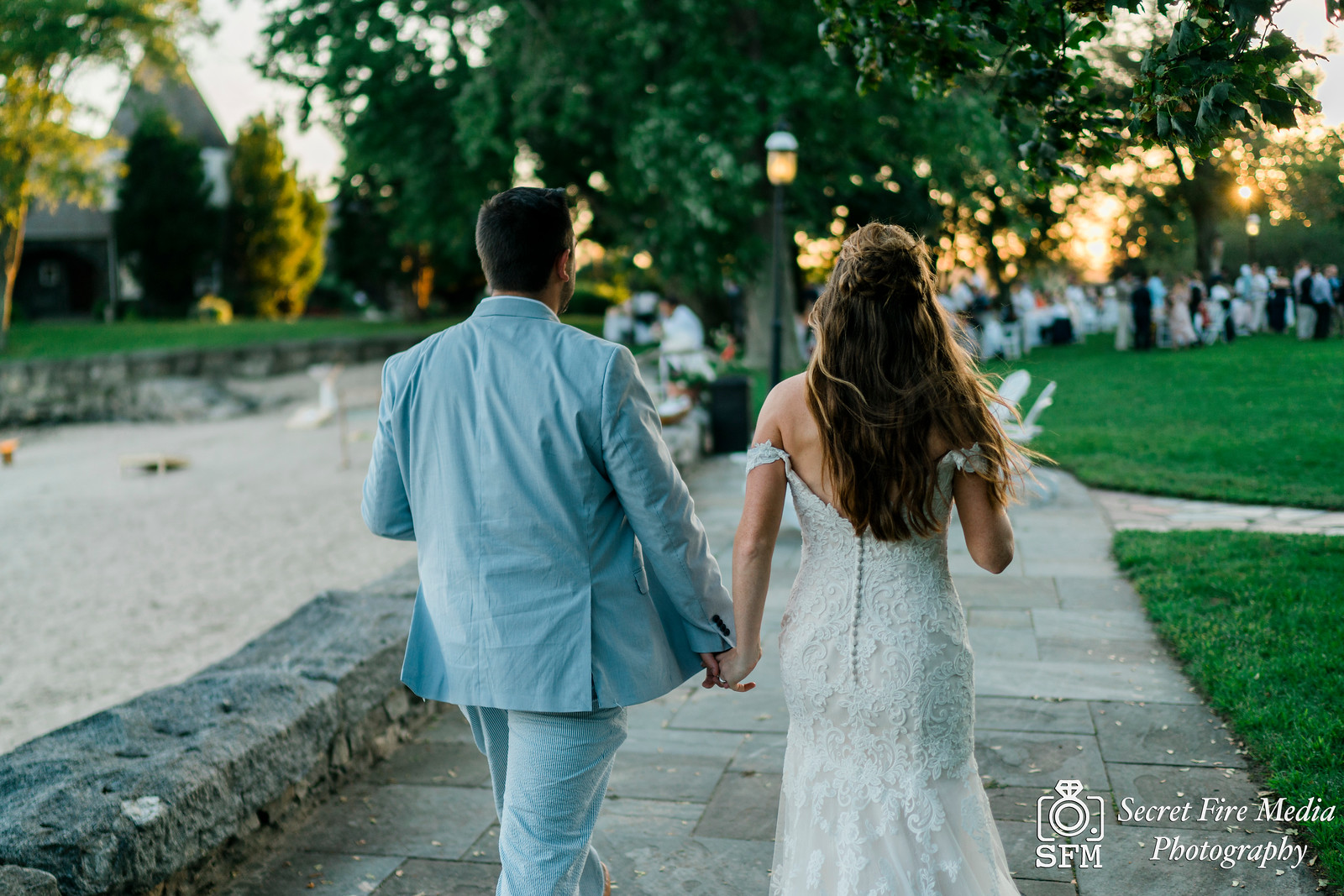 Bride and groom walk at sunset at a Hudson Valley Wedding At Mamaroneck Beach and Yatch Club