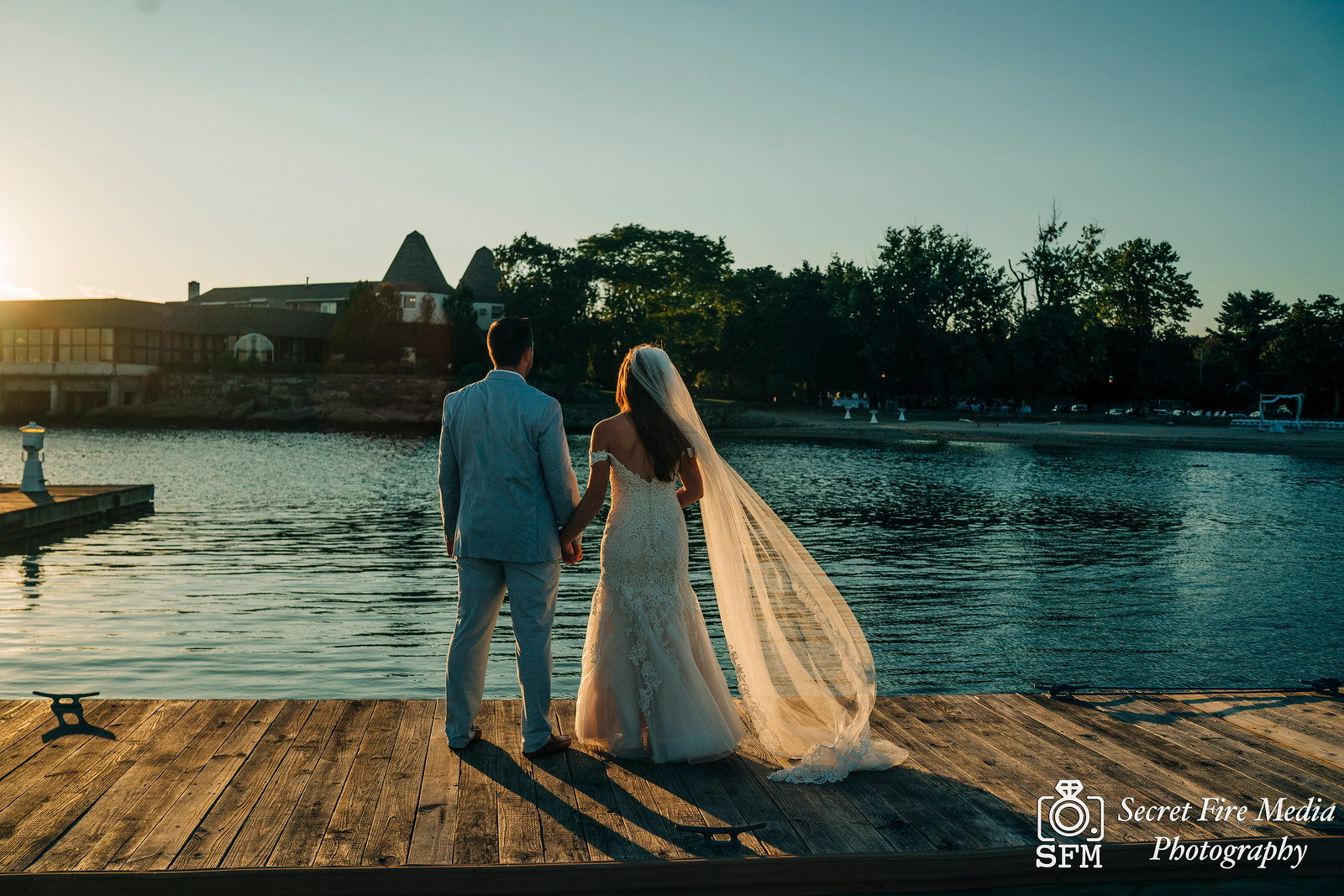Bride and groom look at the water on the dock at a Hudson Valley Wedding At Mamaroneck Beach and Yatch Club
