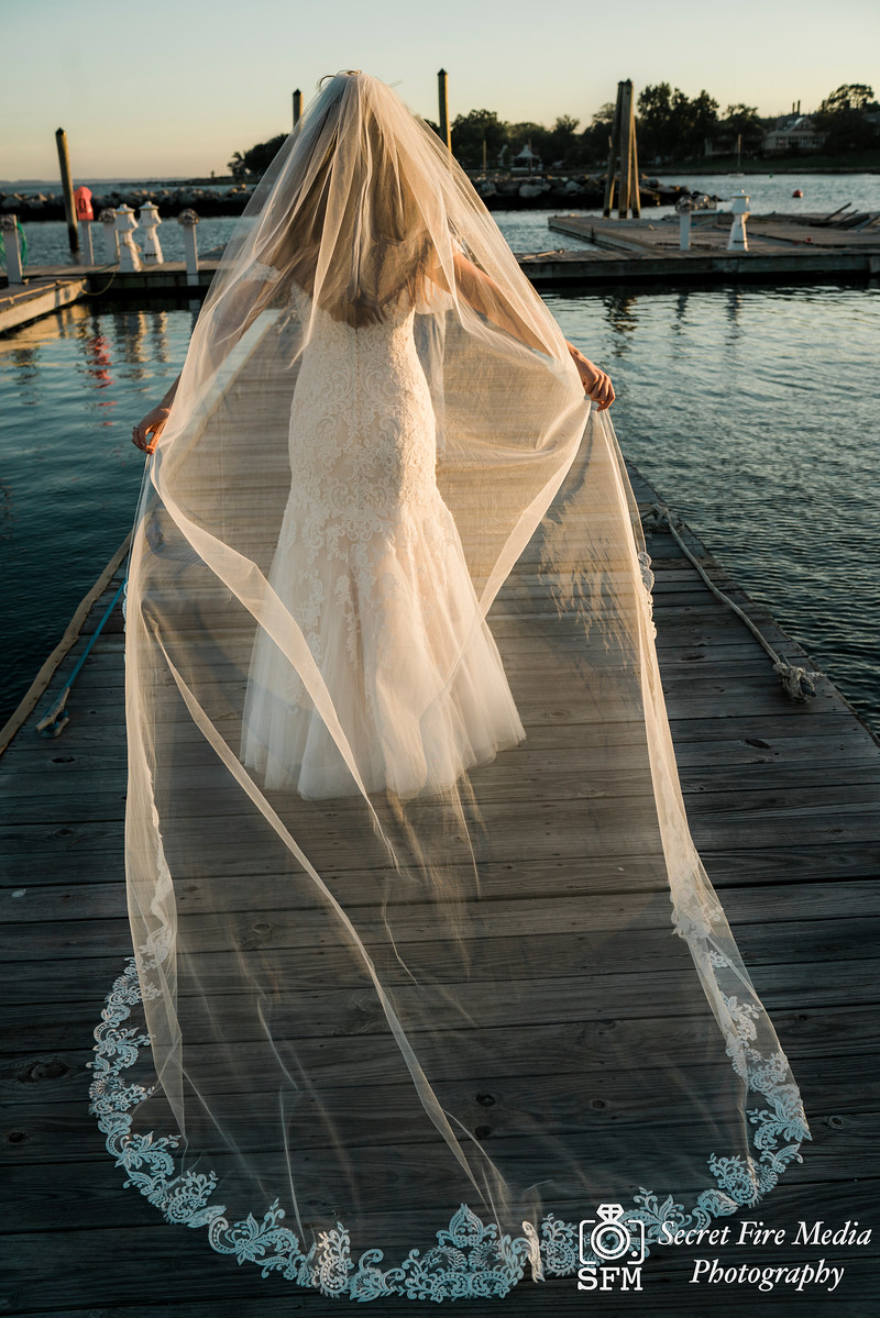 Brides Veil and dress on a dock at a Hudson Valley Wedding At Mamaroneck Beach and Yatch Club