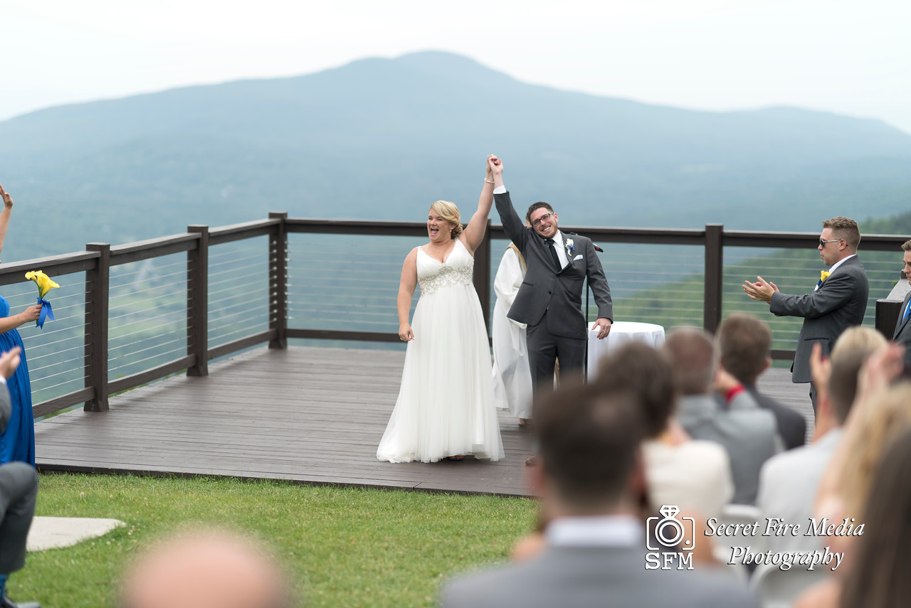 Bride and groom celebrate during their ceremony at a Hudson Valley Wedding At Hunter Mountain in Hunter New York