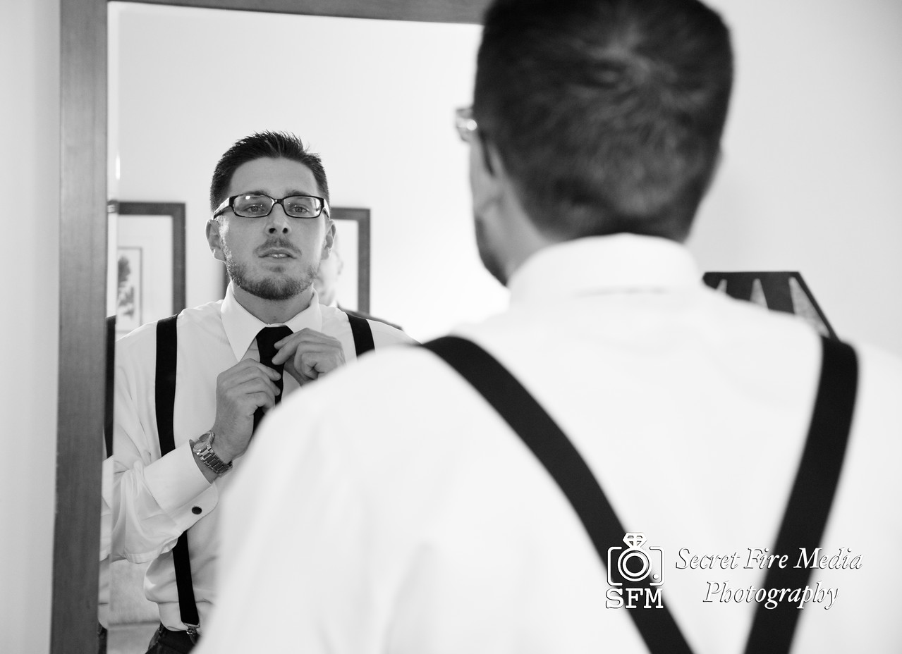 Groom putting on tie while getting ready for his Hudson Valley Wedding At Hunter Mountain in Hunter New York