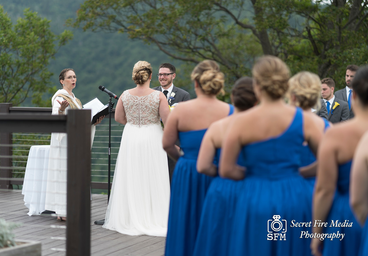 Groom smiles at groom with bridesmaids in background during their ceremony at a Hudson Valley Wedding At Hunter Mountain in Hunter New York
