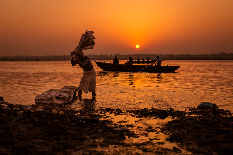 Man doing laundry along the bank of the Ganges River in Varanasi, India