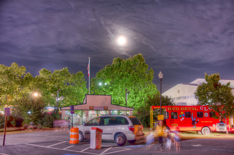 """<h3 style=""""text-align: left;""""><strong>Today's Photo:  Super Moon and the Fair</strong></h3> May 5, 2012 was the super moon for this year.  A super moon is when the moon is at its closest to the earth and it coincides with the full moon.  This causes the appearance of the moon to be much larger than normal.  I spent the evening at the Shrine Circus and Fair at Jim R. Miller park in Marietta Georgia.  I had tons of fun, but it was not the ideal setting for getting shots of the moon.  I was able to get this one of the entrance.  Photography has many artistic abilities due to the technical aspects of how it works.  One of those is the ability to """"compress"""" an image based on the amount of focal length in the lens, for example: through an 18mm lens, objects appear to be farther apart and through a 500mm lens, they appear closer and farther away objects appear larger.  This shot was at 18mm which is why the moon looks small."""