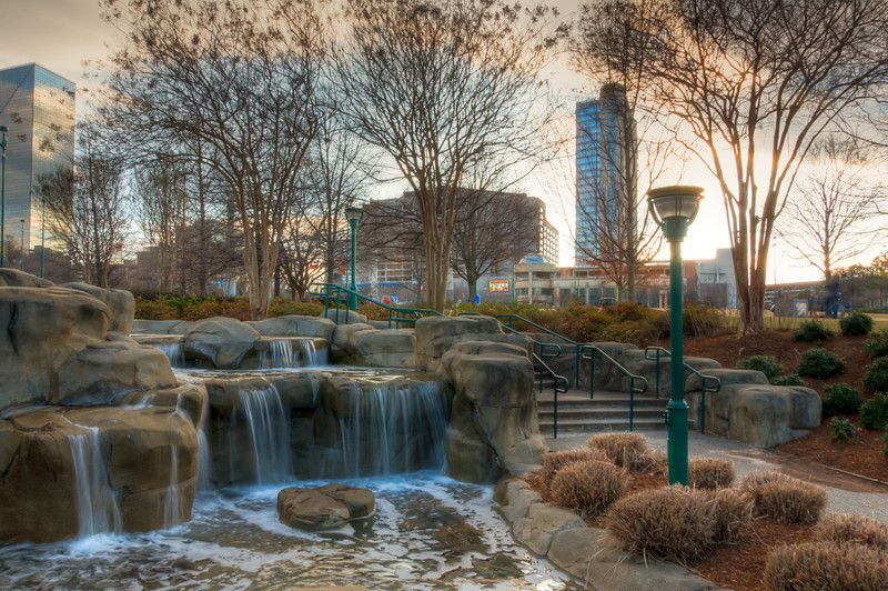 """<h3 style=""""text-align: left;""""><strong>Today's Photo:  Another Olympic Waterfall</strong></h3> Many cities walk a fine line between development and maintaining green space and parks.  Atlanta falls into that category and includes several large parks.  Centennial Olympic Park is one of those parks.  It is a gem of peacefulness amidst the bustle of one of the busiest cities in the world.  My favorite part is not the fountain in the shape of the Olympic Rings, the many monuments or the vast open area to just lay around or have fun, although all of those are nice.  My favorite part of the park happens to be the flowing creek along the eastern edge of the park.  The babbling of the brook seems to make the sounds of downtown melt away and the waterfalls make for an interesting view.  Read more at the <a href=""""http://justshootingmemories.com"""">Daily Photography Blog</a> Just Shooting Memories!..."""