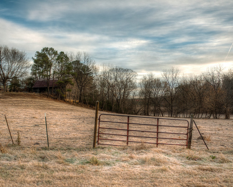 """<h3 style=""""text-align: left;""""><strong>Today's Photo:  Frosty Morning</strong></h3> I have shot so many photos of gates in this area, that sometimes I forget to look elsewhere.  What is sad is that this gate is just down the road from the others.  Most of the time, I don't make it by this gate with good light.  Usually it is too early, as in the sun is not up yet.  That was not the case this morning.  I got there just in time for the sun to rise over the hill beside this gate and barn.  It had been cold enough for frost and the sun had not heated it enough to make it go away.  Read more at the <a href=""""http://justshootingmemories.com"""">Daily Photography Blog</a> Just Shooting Memories!..."""
